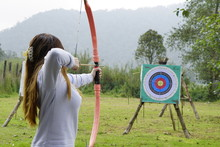 Young Woman Is Aiming In Archery  Practice N The Field With A Target In Front Of Her.