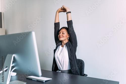 Fotografia Break at work. Female office worker stretching hands.