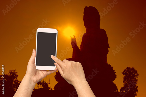 Foto op Canvas Asia land woman hand hold and touch screen smart phone on blurred religion sign.