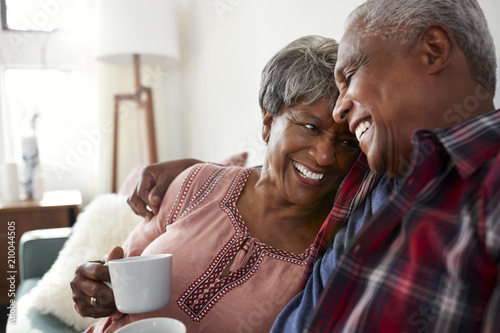 Pinturas sobre lienzo  Loving Senior Couple Sitting On Sofa At Home Relaxing With Hot Drink