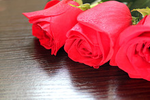 Three Beautiful Red Roses Lying On The Table