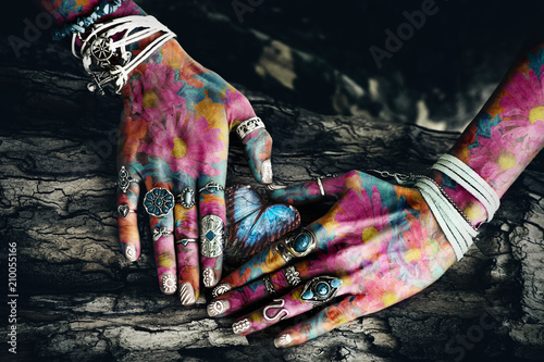 closeup of woman colorful hands on tree surface in heart shape  with butterfly in the middle composite photo