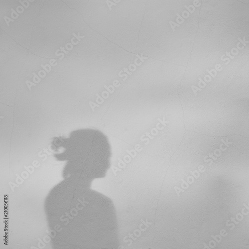 fototapeta na ścianę Shadow of a girl on a white concrete wall