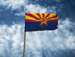 Arizona flag USA flag Silk waving flag made transparent fabric of Arizona US state with wooden flagpole gold spear on background sunny blue sky white smoke clouds real retro photo 3d illustration