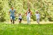 Glückliche Familie und Kinder laufen im Park