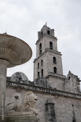 Fotografie, Obraz  Looking at the belfry from behind the lion fountain of the Convento de San Francisco de Asís (Convent of San Francisco of Asis) in the Plaza of San Francisco in Old Town Havana (Habana Vieja)