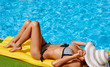 Portrait of beautiful tanned woman relaxing in bikini and hat in swimming pool. Gel polish red manicure. Hot summer day and bright sunny light.