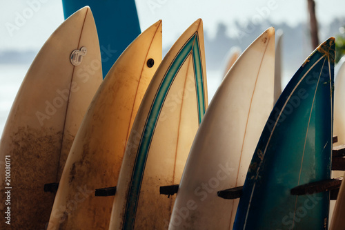 Valokuvatapetti Set of different color surf boards in a stack by ocean
