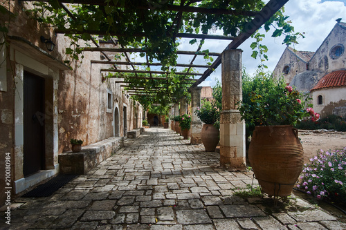Fotografie, Obraz Blooming flowers in the courtyard of the historic Orthodox monastery Moni Arcadia on the island of Crete
