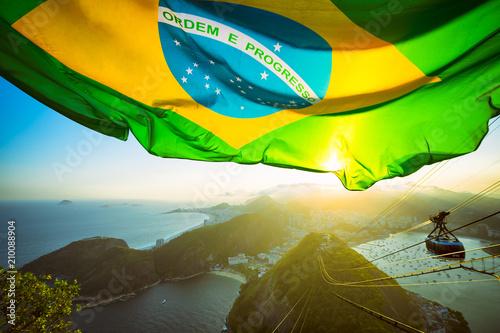 Photo sur Toile Brésil Brazilian flag shines above the golden sunset city skyline at Sugarloaf Mountain in Rio de Janeiro Brazil.
