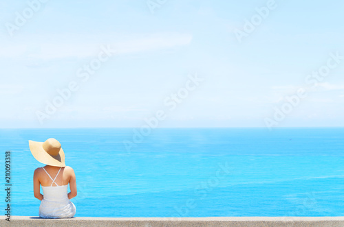 Fotobehang Zee / Oceaan Elegant woman with white dress and white hat enjoys the view over the sea summer concept
