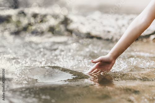Fotografering  Concept of Environment,Natural Touch,Hand touches the water in nature,copy space