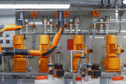 Photo Orange pumps are in a row. Concept: industrial equipment