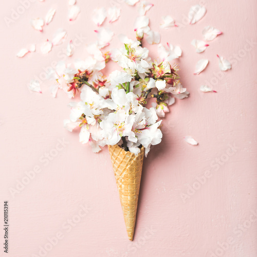 Flat-lay of waffle sweet cone with white almond blossom flowers over pastel light pink background, top view. Spring or summer mood concept, square crop