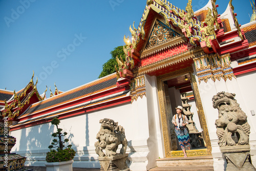 Staande foto Bedehuis Asian woman stepping out the gate if temple