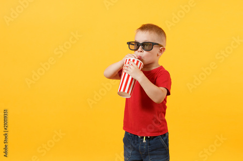 Little cute kid baby boy 3-4 years old in red t-shirt, 3d imax cinema glasses holding plastic glass of soda, drinking cola isolated on yellow background Canvas Print