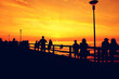 Silhouettes of many people standing on sea bridge and looking at sunset. Silhouette of tourists and beach bridge on sunset.