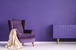 canvas print picture - Vintage armchair, beige blanket and cabinet set on a violet wall in a living room interior