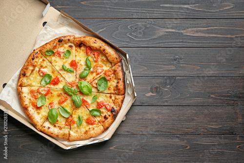 Fotografia Carton box with delicious pizza Margherita on wooden background