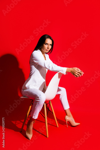 Studio Posing Snap Photoshooting Concept Portrait Of Stunning Cool Woman Sitting On Chair Looking At Camera Isolated On Vivid Red Background Kaufen Sie Dieses Foto Und Finden Sie Ahnliche Bilder Auf