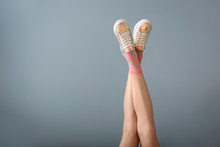 Legs Of Beautiful Young Woman On Color Background