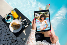 Woman Relaxing By The Pool And Reading Emagazine On Tablet At Breakfast. All Contents Are Made Up.