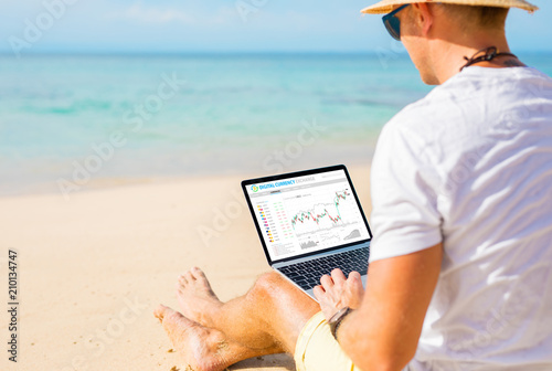 Foto Man trading cryptocurrencies on the beach.