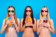 Leinwanddruck Bild Portrait of cool trio drinking colorful cocktails from tubule looking at camera isolated on vivid blue background. Bar holiday celebration concept