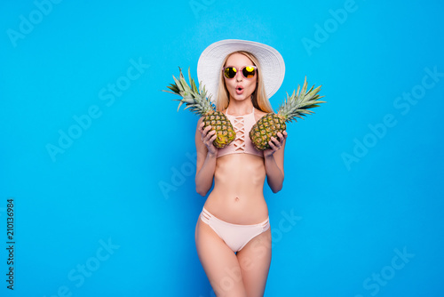 Fototapeta Portrait of comic funny girl with slender figure in pink two pieces swimsuit closing tits with two pineapples isolated on bright blue background