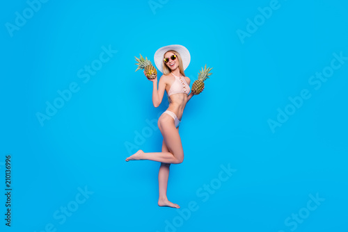 Obraz Fullbody concept of pretty fit girl in eyewear two pieces swimsuit holding raised thin leg having two fresh pineapples in hands enjoying sunshine isolated on bright blue background - fototapety do salonu