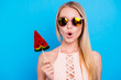 canvas print picture Pop nutrition healthy lifestyle calories concept. Portrait of shocked wondered girl in eyewear holding sweet piece of watermelon on stick isolated on vivid blue background
