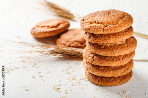 Papiers peints Biscuit A stack of oatmeal cookies with oat flakes on a white wooden table