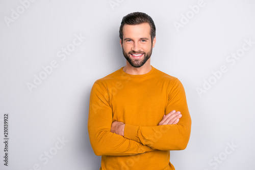 Portrait of attractive self-assured with beaming shiny smile haircut with long furfur wearing casual classic color of mustard sweater macho man standing with folded arms isolated on gray background