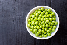 A Seeds Of Peas In A Bowl On Wooden Background. Copy Space