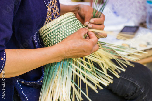 Fototapeta Motion Image - hand of woman holds The villagers took bamboo stripes to weave into different forms for daily use utensils of the community's people in Bangkok Thailand, Thai handmade product