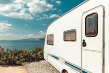 Caravan Trailer Near Sea, Beach And Blue Sky. Summer Holidays Road Trip Travel Concept