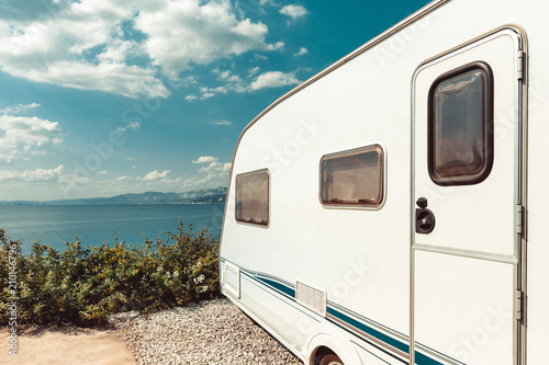 Caravan Trailer Near Sea, Beach And Blue Sky. Summer Holidays Road Trip Travel Concept