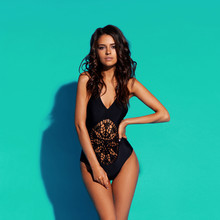 Young Sexy Slim Tanned Woman In Black Swimsuit Posing Against Blue Background. Fashion Portrait Of Beautiful Girl With Long Wavy Brunette Hair. Swimwear Or Bikini Model