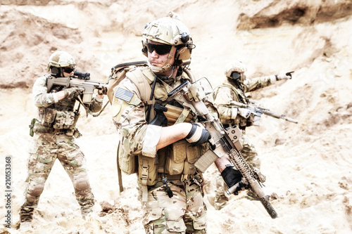 Obraz na plátně Group of well equipped US army commandos armed with assault rifles, moving through sandy terrain or desert