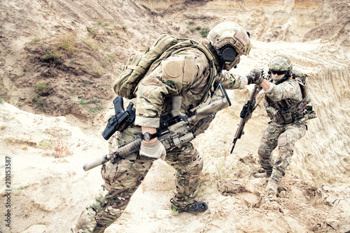 Fotografía  US ranger, modern infantryman, special reconnaissance team member or military scout in ammunition, armed with service rifle helping brother in arms to climb on sand dune