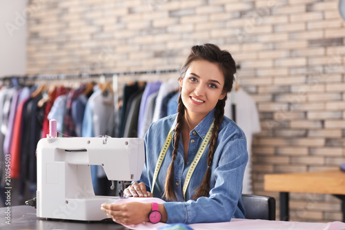Young female tailor using sewing machine in atelier Canvas Print