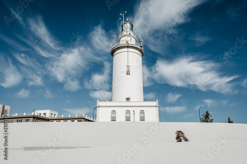 Montage in der Fensternische Leuchtturm White lighthouse with blue sky background, and people walking in the street.