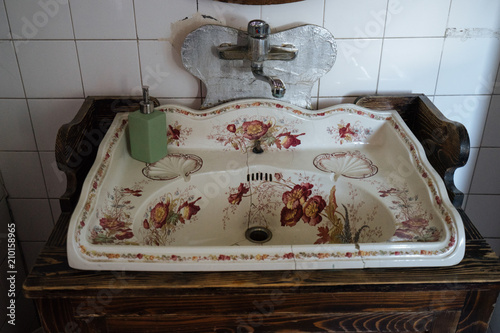 old cracked white sink with floral ornament