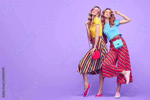 Full-length portrait Two Girls with Wavy Hairstyle Having Fun Dance. Young Beautiful Pretty Model Woman in Striped Fashion Stylish Summer Outfit. Crazy Sisters Friends on Purple