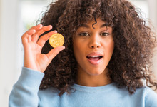 African American Woman Holding Golden Bitcoin Cryptocurrency At Home Scared In Shock With A Surprise Face, Afraid And Excited With Fear Expression