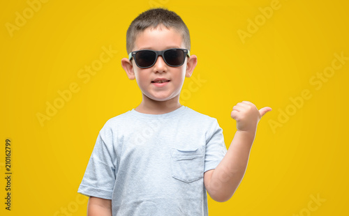Fototapeta  Dark haired little child wearing sunglasses pointing with hand and finger up wit