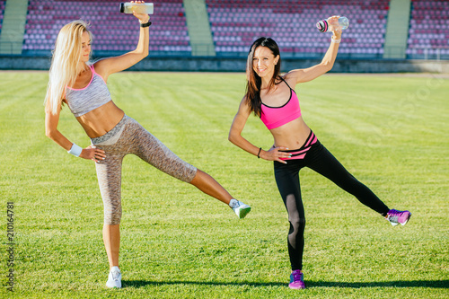 32cfef1ea4 Two happy young girlfriends warm up legs together outdoors. Two slim sporty  women standing in one-legged pose and holding bottle with water like a  dumbbell ...