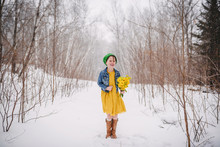 Girl Standing In The Snow Holding A Bunch Of Flowers