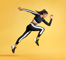 Sporty woman running on yellow background