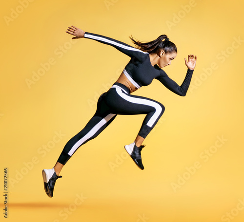 Sporty woman running on yellow background Canvas Print